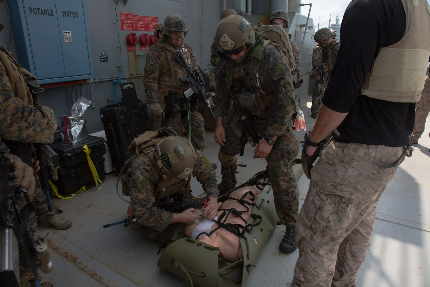 U.S. Marines with the Maritime Raid Force (MRF), 26th Marine Expeditionary Unit (MEU), provide care to a simulated casualty during visit, board, search and seizure (VBSS) training at Fort Eustis, VA.