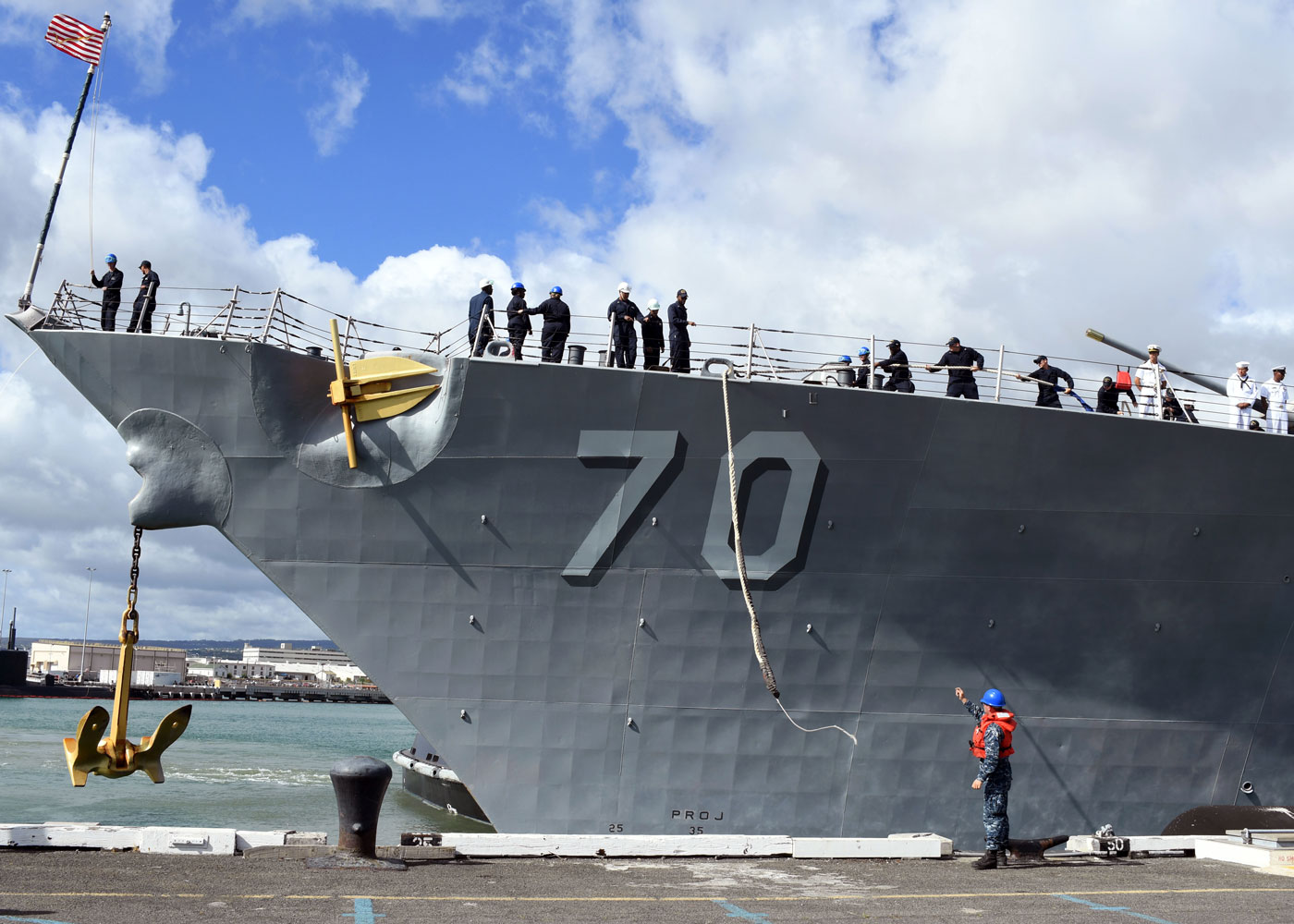 Line handlers aboard guided-missile destroyer USS Hopper tow in the ship's mooring lines as the Hopper prepares to depart Joint Base Pearl Harbor-Hickam for its independent deployment to the Western Pacific and Middle East.