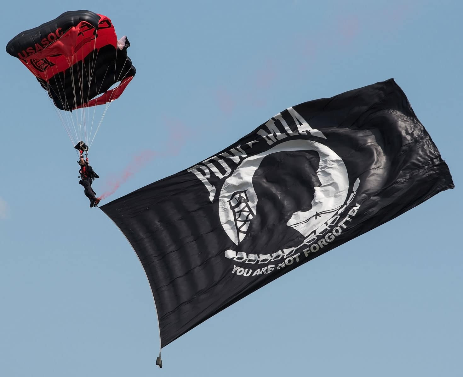 "A member of the Black Daggers, U.S. Army Special Operations Command's Parachute Demonstration Team, glides down with the POW-MIA flag during ""Thunder Over Dover: 2017 Dover AFB Open House"" opening ceremony, on Dover Air Force Base, Delaware."