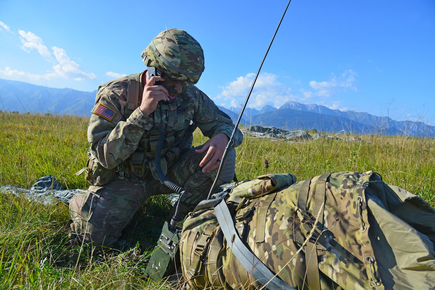 A United States Army Paratrooper assigned to the 173rd Brigade Support Battalion, 173rd Airborne Brigade, conducts a radio check during an airborne operation onto Frida Drop Zone in Pordenone, Italy.