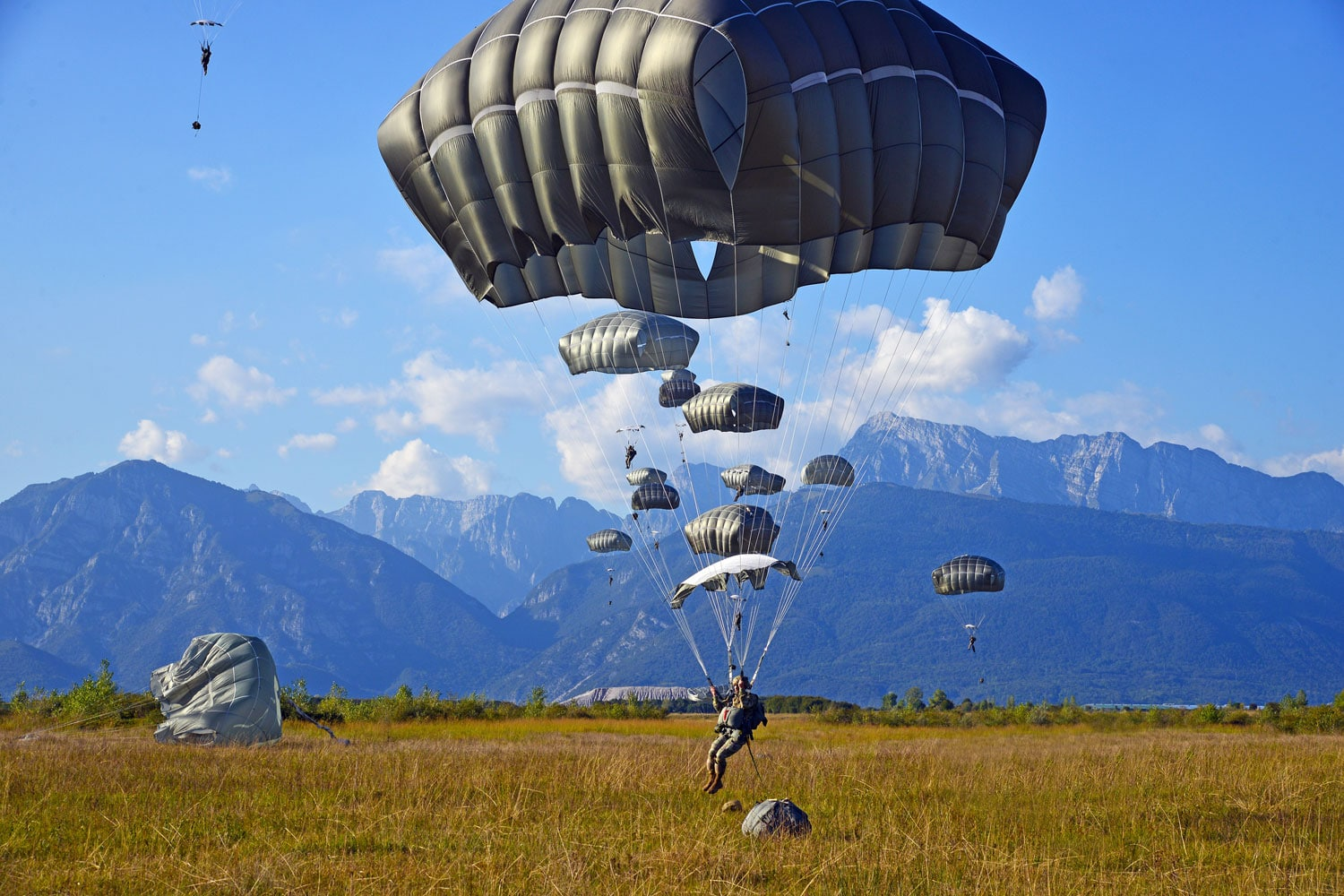 U.S. Army Paratroopers assigned to the 173rd Brigade Support Battalion, 173rd Airborne Brigade, prepare to land after exiting a U.S. Air Force 86th Air Wing C-130 Hercules aircraft during airborne operations at Frida Drop Zone in Pordenone, Italy.