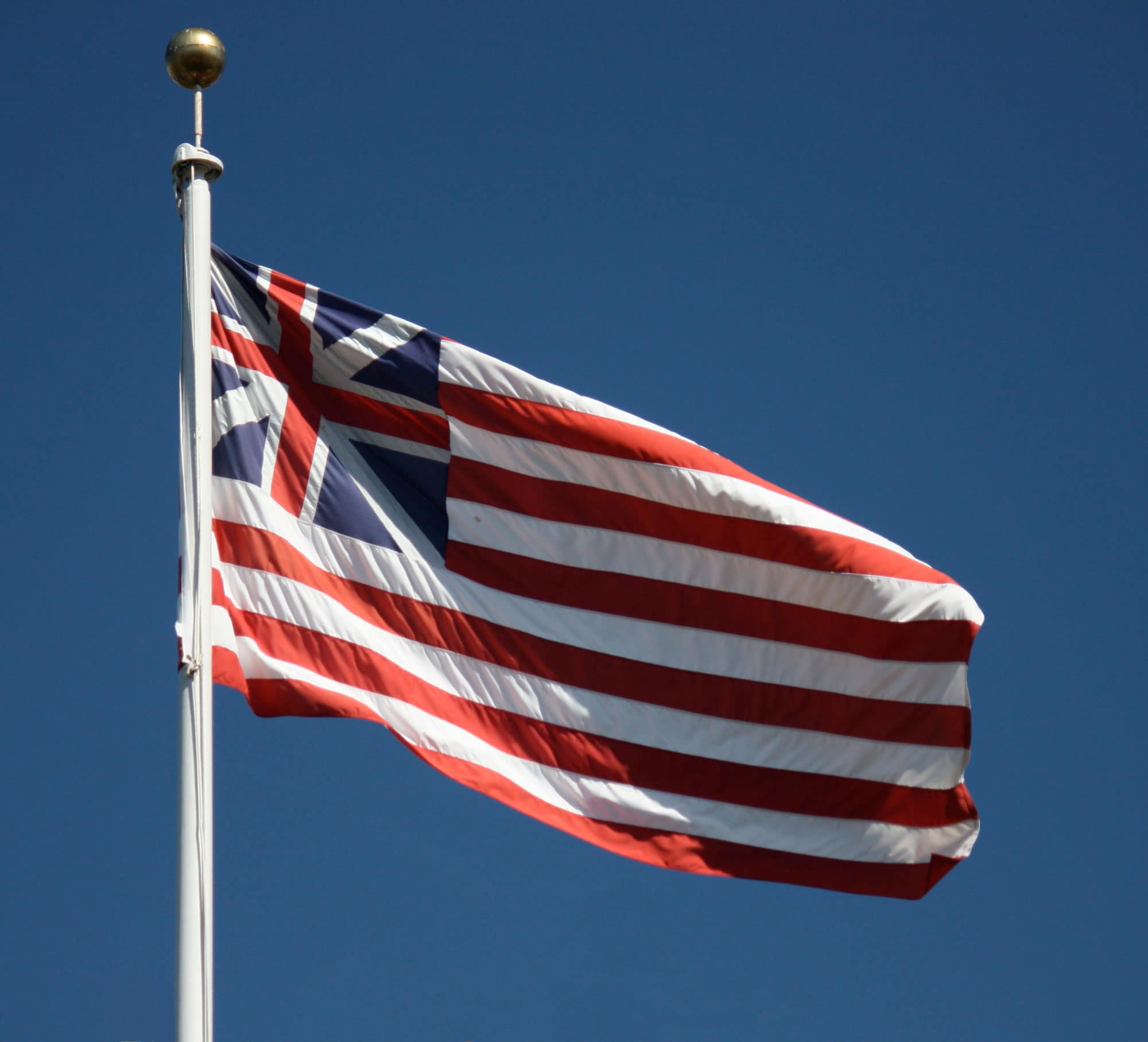 The Grand Union Flag consisting of thirteen alternate red and white stripes -the same as its immediate successor, the first national flag of the United States.