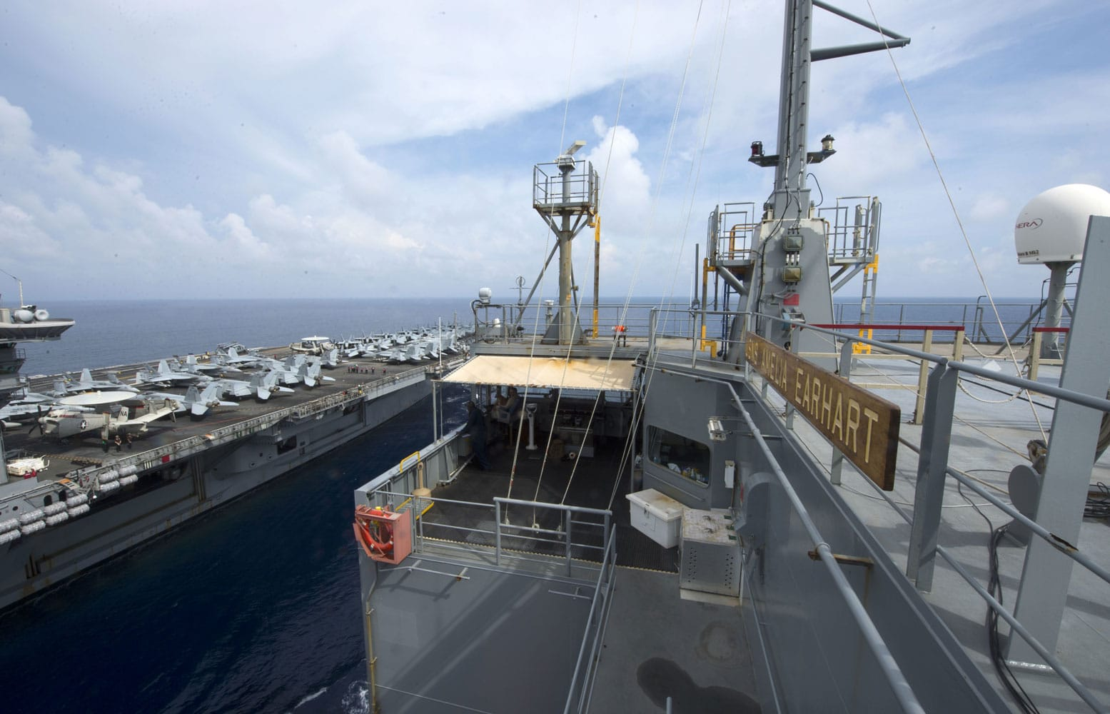 Military Sealift Command dry cargo and ammunition ship USNS Amelia Earhart maneuvers alongside USS Theodore Roosevelt during a replenishment at sea in the Western Pacific. Amelia Earhart aids the U.S. Navy mission by delivering food, fuel and supplies to Navy vessels, thus extending the Navy vessel's ability to stay at sea.