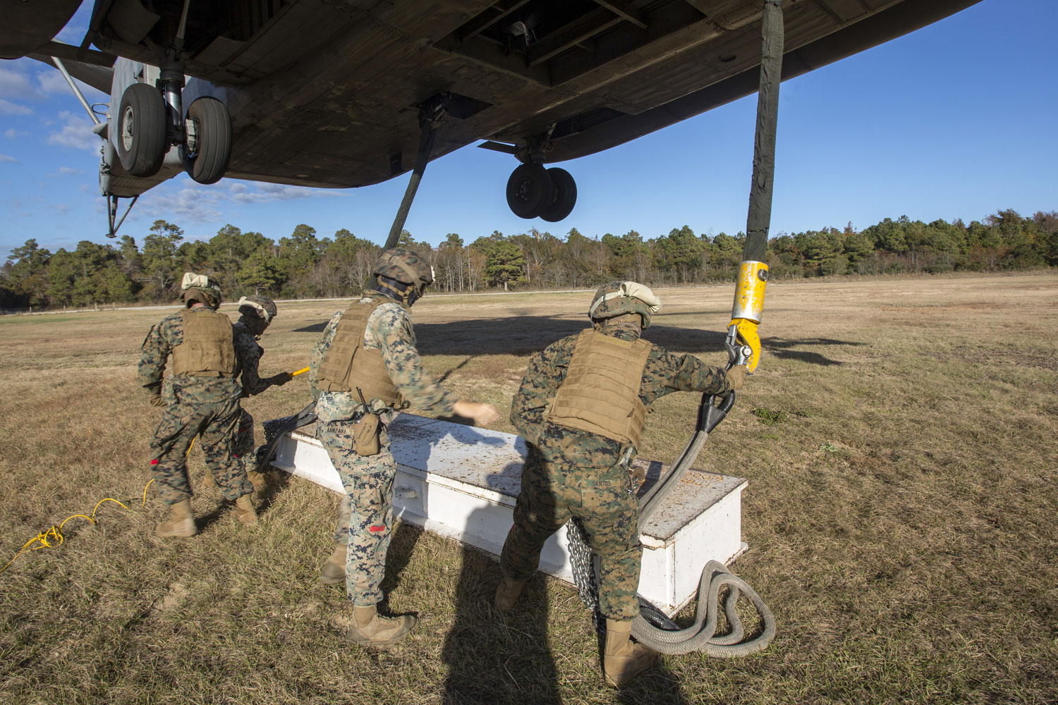 Marines with Combat Logistics Battalion 6, 2nd Marine Logistics Group attach cables and practice materials to a CH-53E Super Stallion during Helicopter Support Team training at Camp Lejeune, N.C.