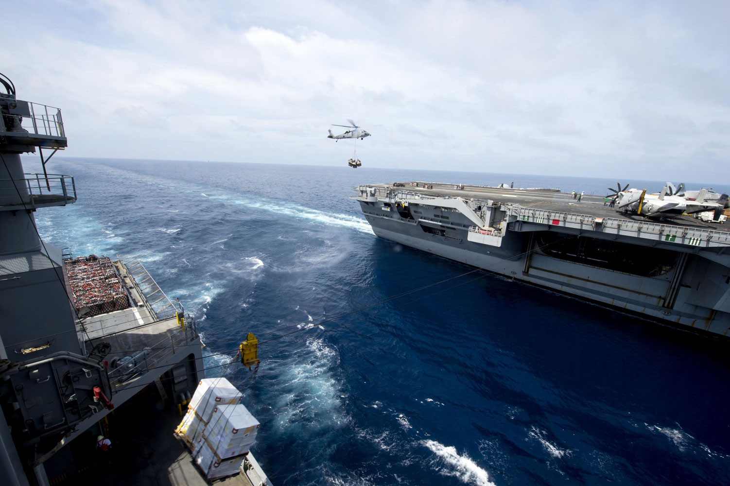 Military Sealift Command dry cargo and ammunition ship USNS Amelia Earhart simultaneously conducts connected and vertical replenishments at sea with USS Theodore Roosevelt in the Western Pacific. Amelia Earhart aids the U.S. Navy mission by delivering food, fuel and supplies to Navy vessels, thus extending the Navy vessel's ability to stay at sea.