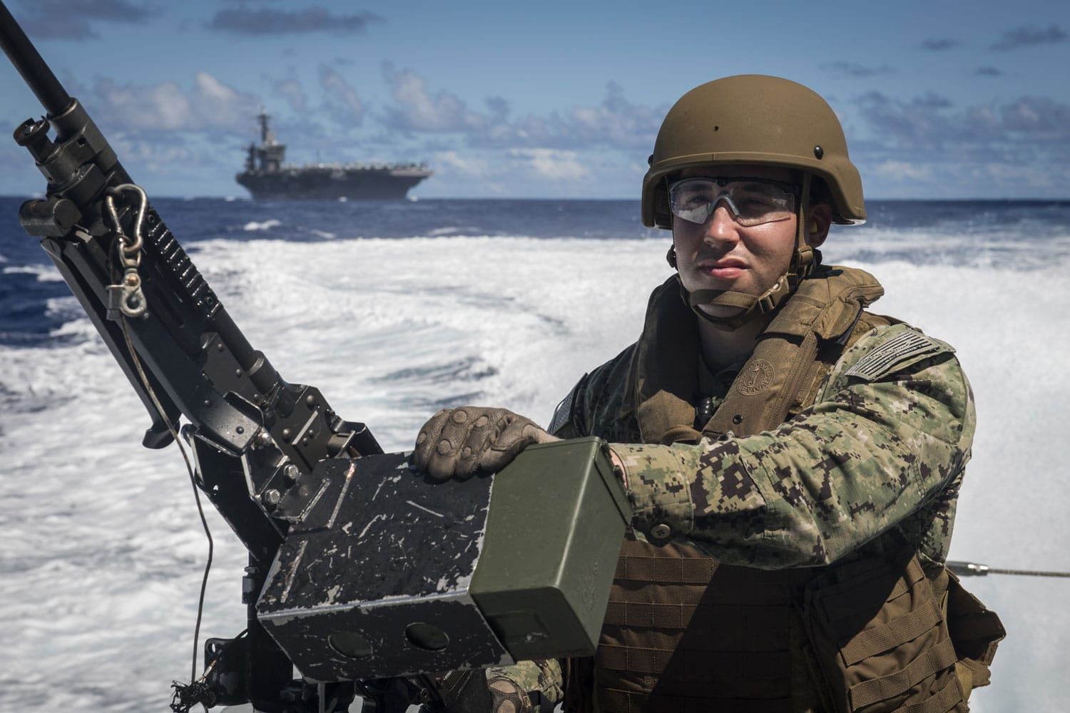 U.S. Navy Electricians Mate 3rd Class Louis Cabiran, assigned to Coastal Riverine Squadron (CRS) 2, mans an M240G machine gun aboard a MK VI patrol boat while providing high value asset protection for the aircraft carrier USS Theodore Roosevelt.