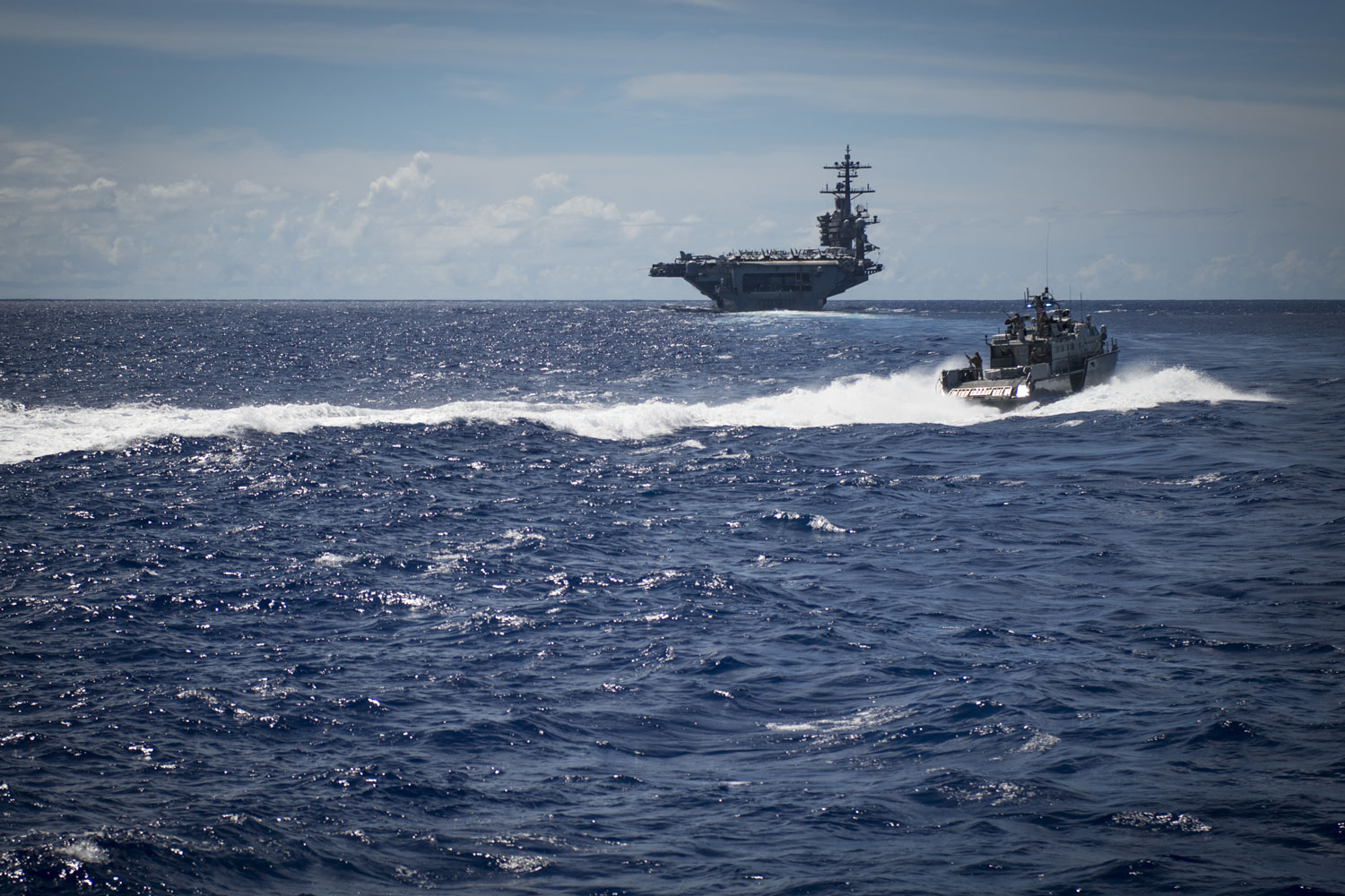 Sailors assigned to Coastal Riverine Squadron 2, aboard a MK VI patrol boat, provide high value asset protection for the aircraft carrier USS Theodore Roosevelt as it transits to Apra Harbor, Guam.