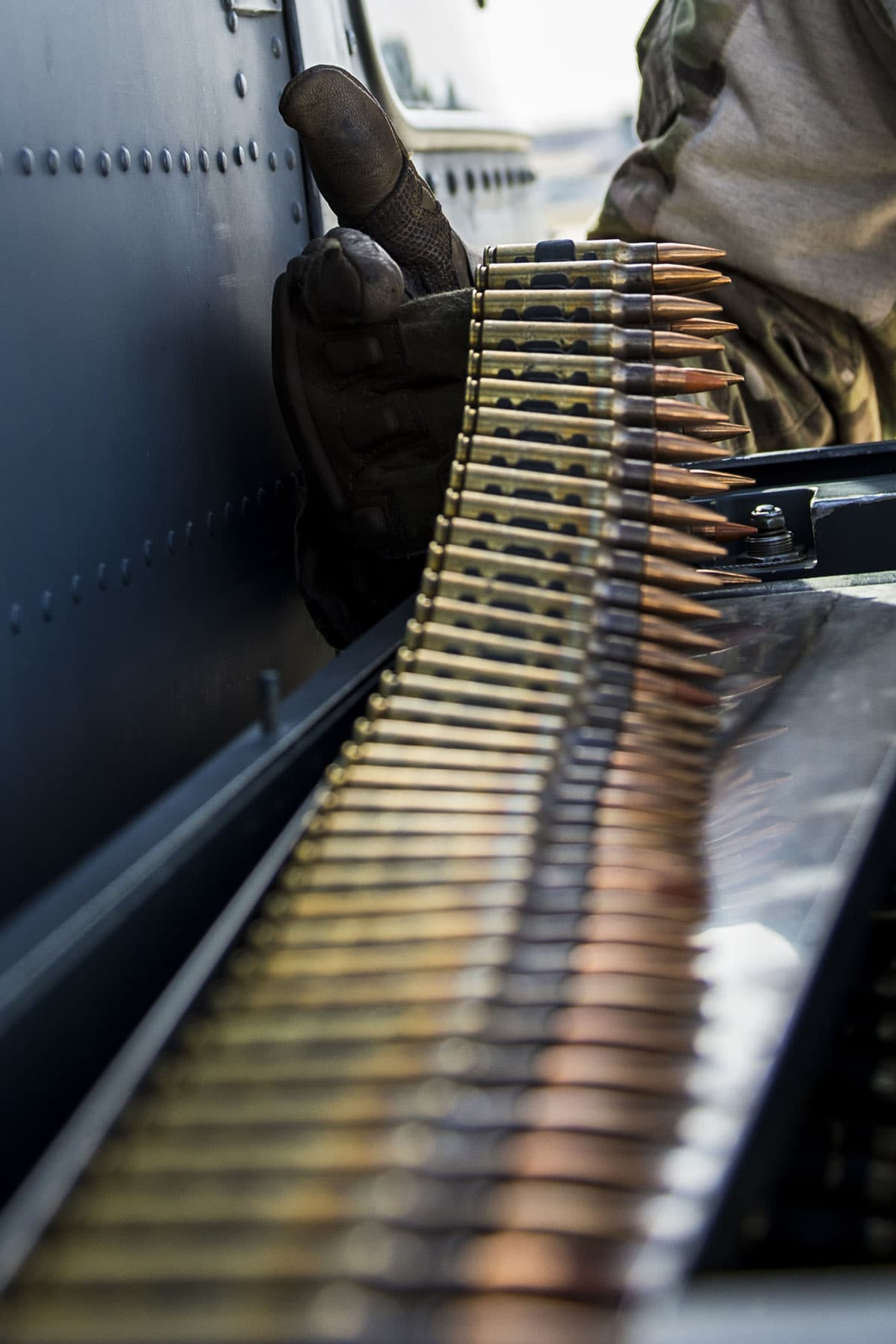 Air Force Master Sgt. Trevor Stevens, from the 943rd Rescue Group, checks the 7.62 mm rounds for an M134 minigun attached to a HH-60G Pave Hawk helicopter.
