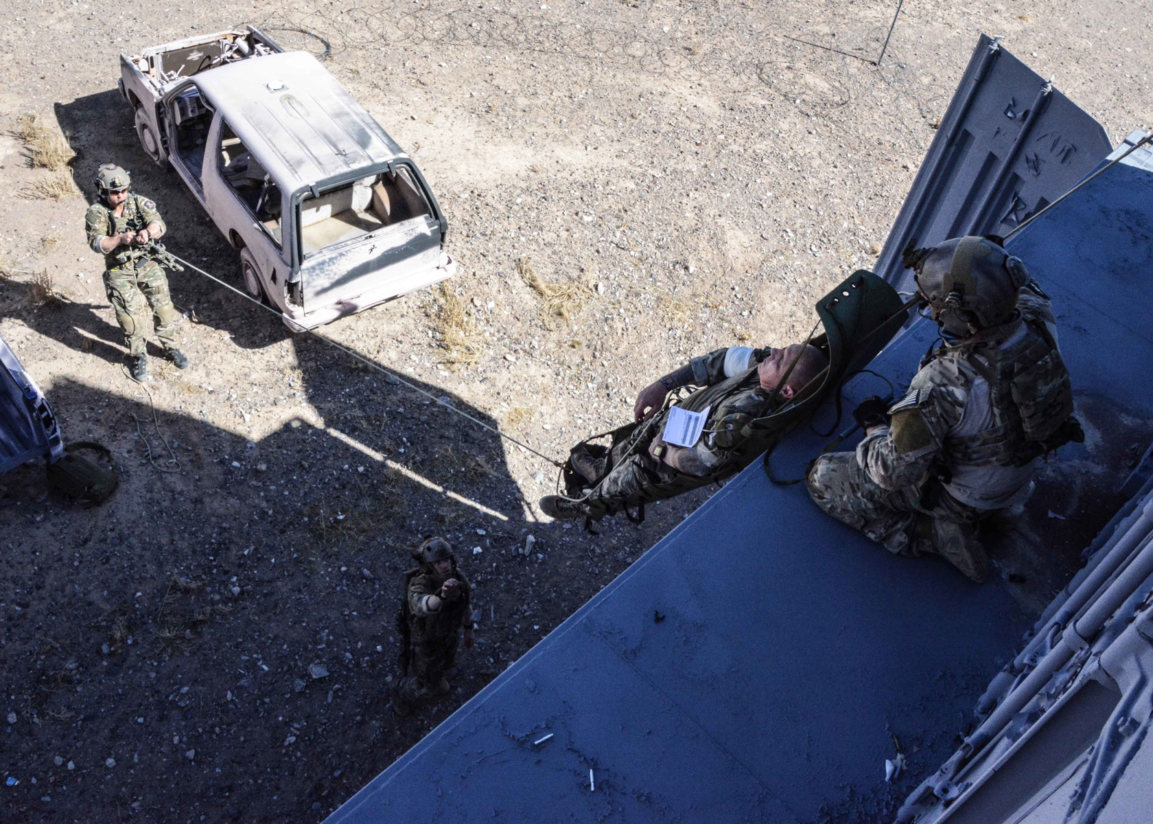 Green Berets from 10th Special Forces Group (Airborne) and a U.S. Air Force Pararescueman lower a simulated casualty during a training exercise.