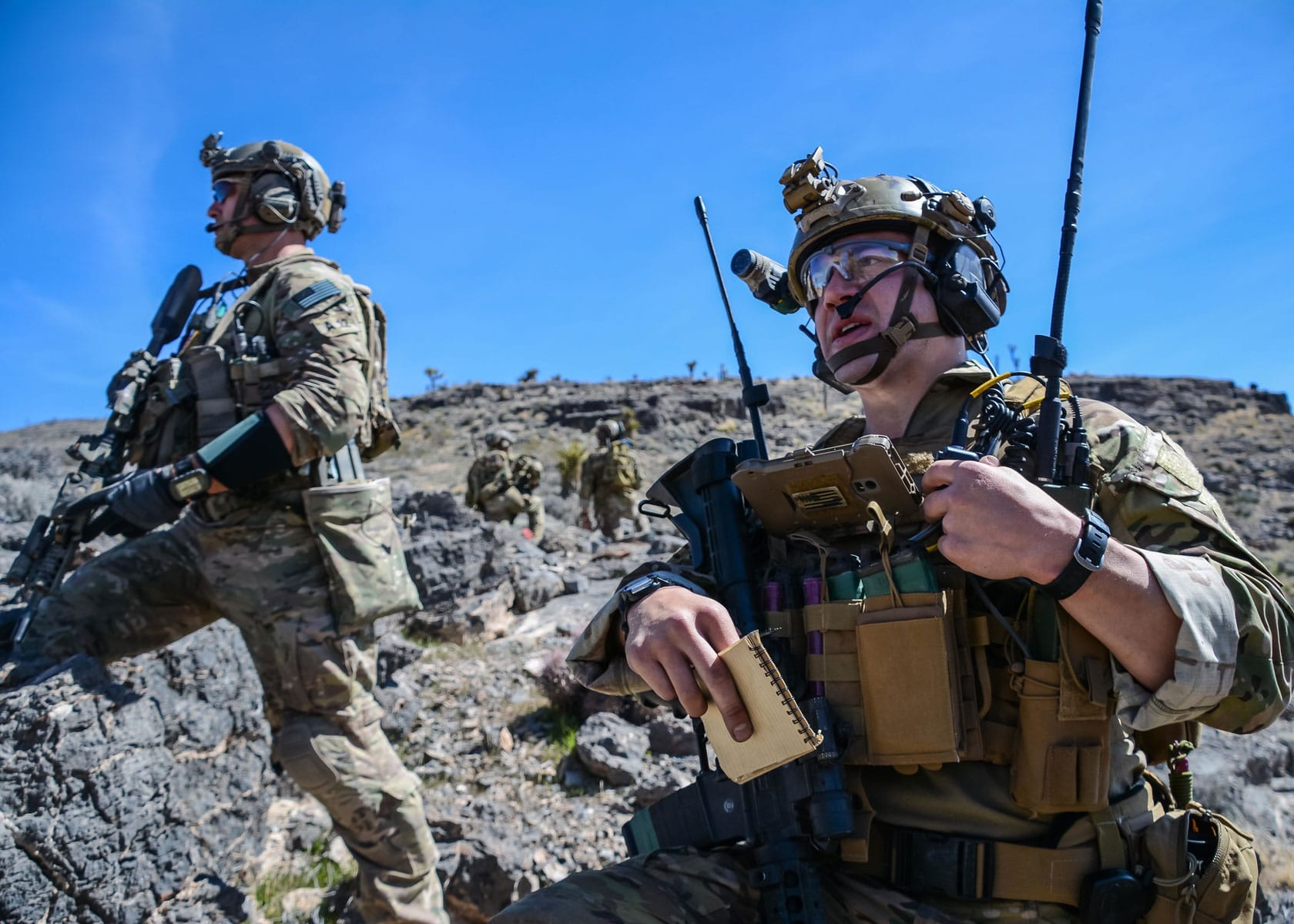 A U.S. Air Force Joint Terminal Attack Controller directs fire during a training exercise as a Soldier with 10th Special Forces Group (Airborne) provides overwatch security.
