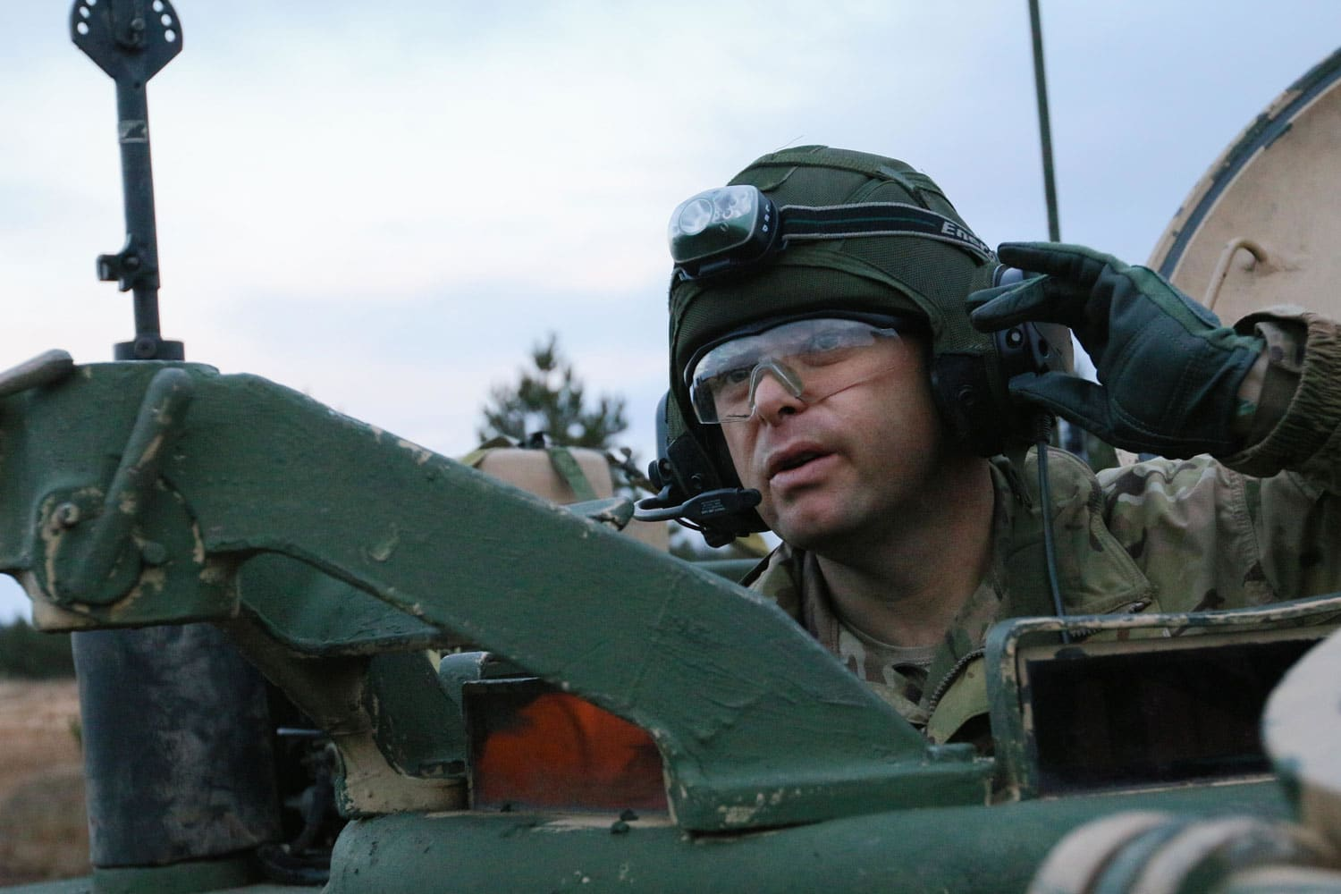 "U.S. Army Capt. Matt Eley, a Carey, Ohio native and the commander of ""Tomahawk"" Company, 5th Squadron, 4th Cavalry Regiment, 2nd Armored Brigade Combat Team, 1st Infantry Division, receives information on his headset regarding the movements of his Soldiers during training in Adazi, Latvia."