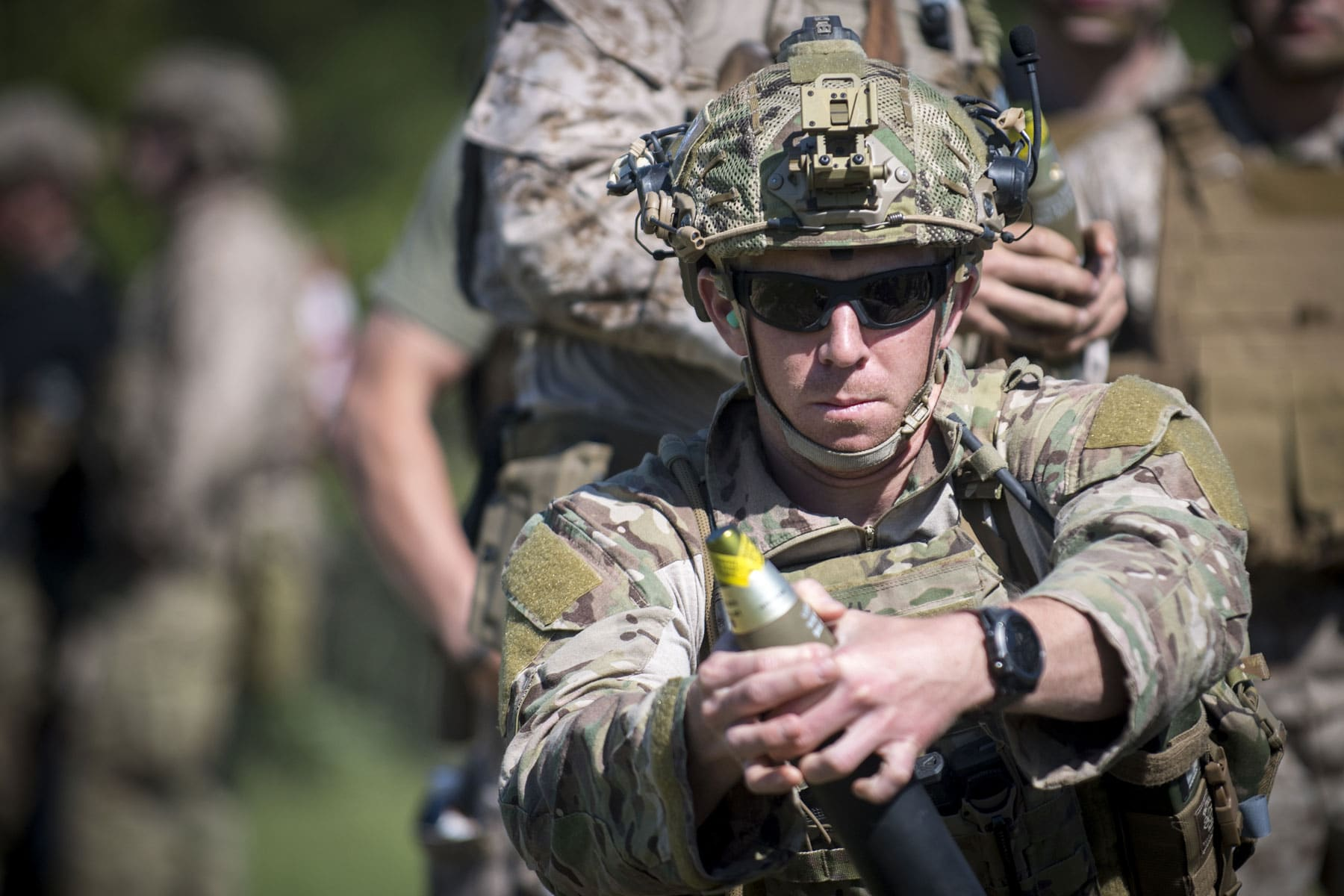 A partner force member hangs an M888 mortar round into a M224 60mm Mortar during indirect-fire training.