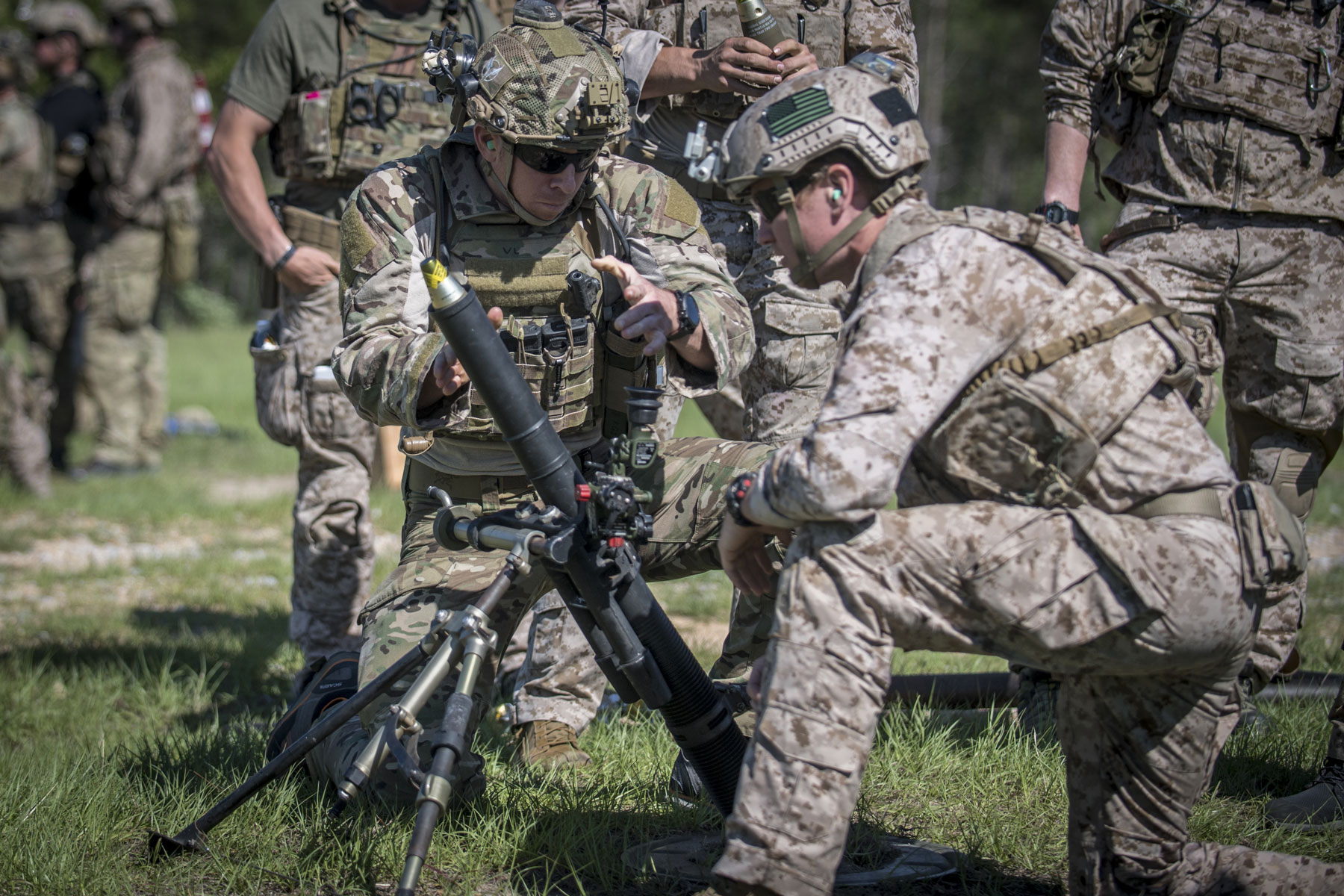 A partner force member drops an M888 mortar round into a M224 60mm Mortar during indirect-fire training.