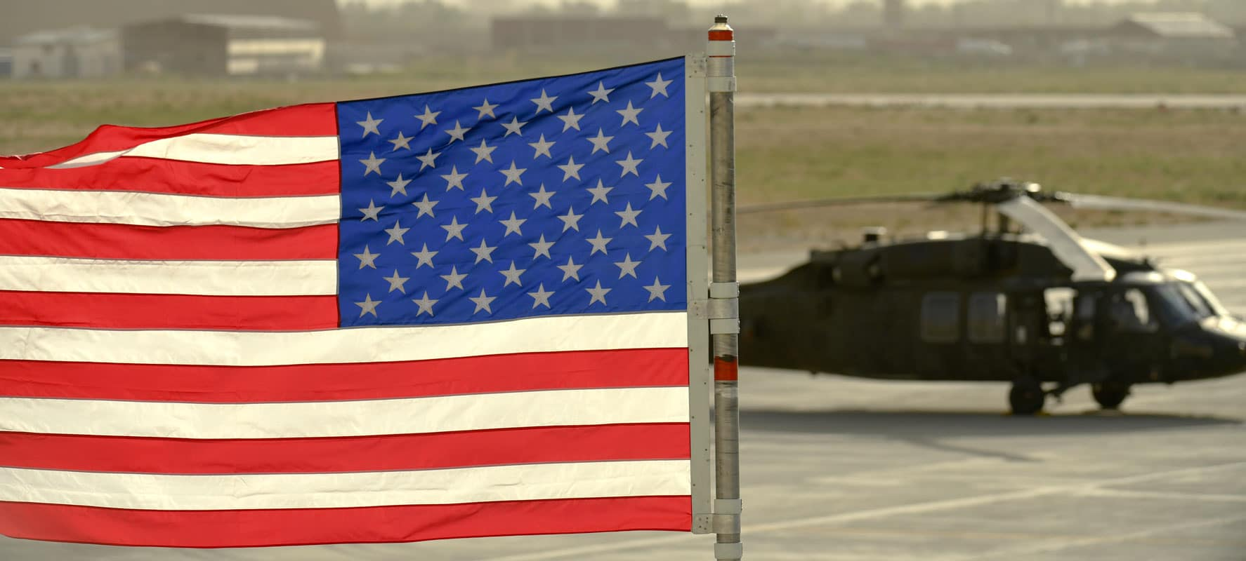 (Bagram, Afghanistan) The American flag waves in the wind with a UH-60 Blackhawk helicopter assigned to Task Force Shadow parked on the flight line.