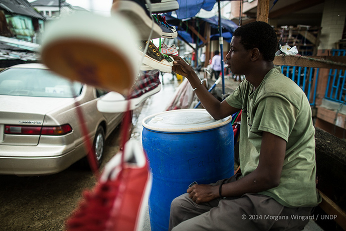 Ibrahim, 20, sells shoes in Waterside Market in downtown Monrovia on Sept. 18, 2014