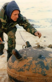 An Explosive Ordnance Disposal (EOD) technician examines an Iraqi mine that washed ashore in the Kuwaiti port of Ash Shuaybah during the Gulf War in 1991. Naval Institute Photo Archive.