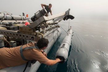 Sailors unload an underwater unmanned vehicle during mine countermeasures training operations aboard the USS Ponce (AFSB(I)-15)