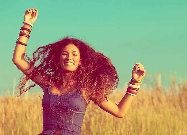 smiling young woman with long curly hair jump  in yellow summer