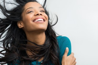 Closeup of smiling young woman with hair in the wind