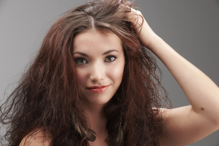 woman grabbing her tangled hair in frustration on grey background