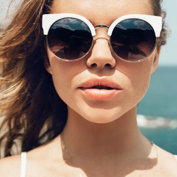 Closeup fashion summer portrait of pretty young sensual woman in sunglasses posing on the beach on vacation ** Note: Soft Focus at 100%, best at smaller sizes
