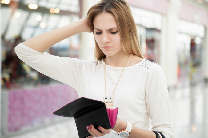 Portrait of unhappy young woman looking in her wallet in shopping center spent too much not enough cash lost money broke