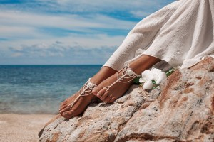 closeup photo of beautiful young bride legs with anklets with beach background
