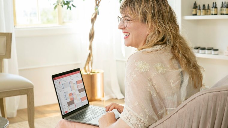 Bloom spa owner Rebecca using Vagaro software on laptop