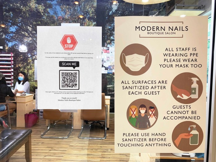 signs of safety measures posted outside the nail salon
