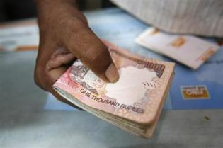 A customer hands bundle of Indian Rupee currency notes to teller at financial institution in Mumbai