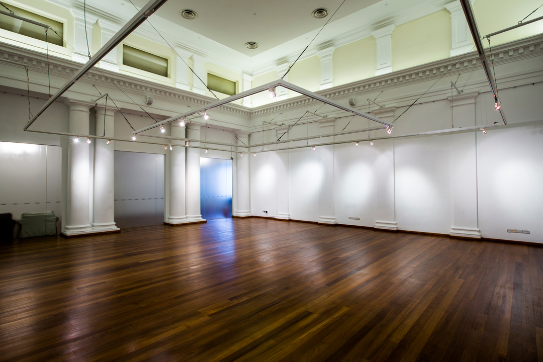 spacious hall with wooden floor and high ceiling