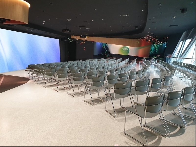 large seminar venue in singapore with big screen and grey audience chairs