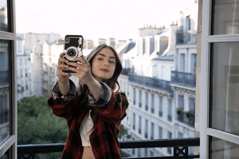lily collins taking a picture in paris balcony