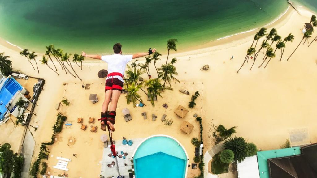 a man do bungy jump in sentosa singapore with beach view and pool below