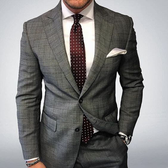 man in a grey suit and tie outfit
