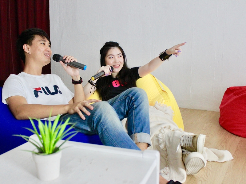 man and woman are doing karaoke session while sitting on the beanbag