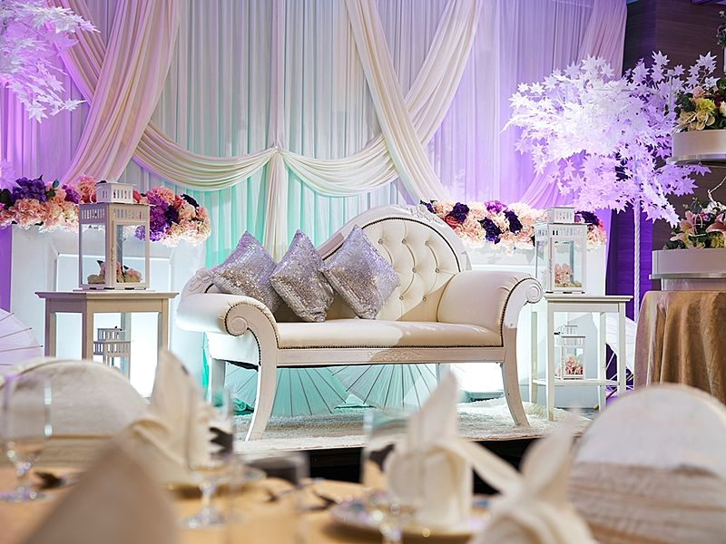 White sofa and silver cushions against white curtain background