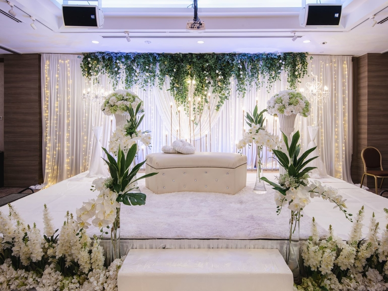 Function venue with white sofa and white floral decoration and fairy lights