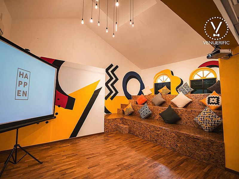Room with wooden steps, throw pillows and projector screen