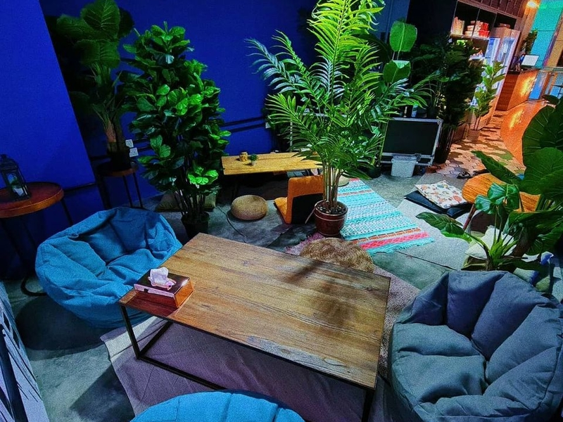 A wooden coffee table with blue beanbags and green plants