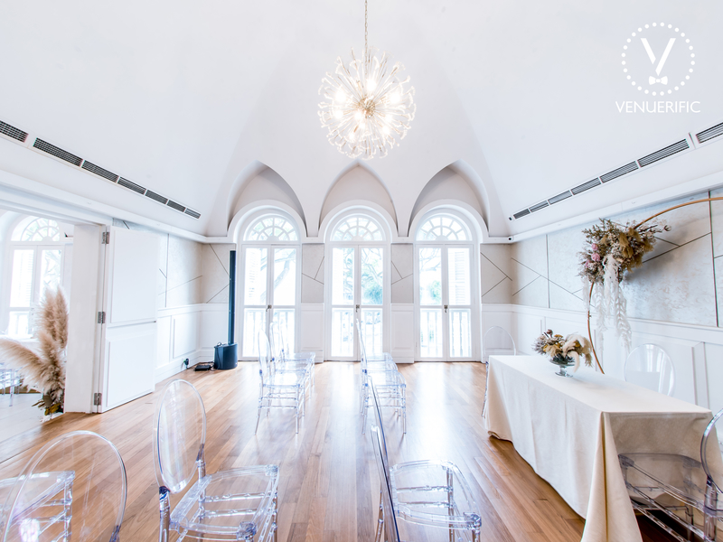 White spacious room with hardwood floors and chandelier