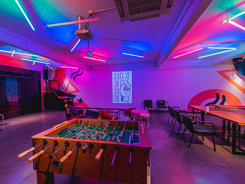 A foosball table in an event space with mood lighting and projector screen