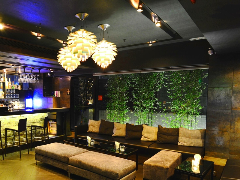indoor bar seating area with plants and warm lights