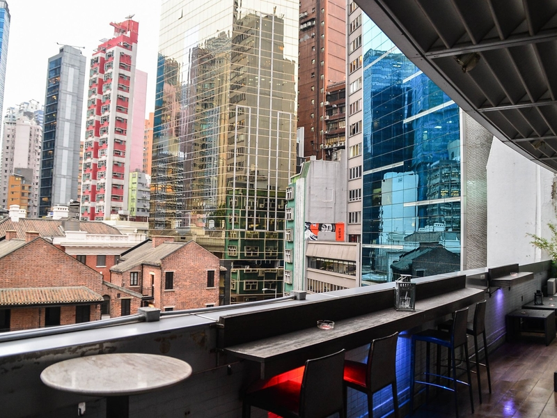 outdoor seating in a bar with a view of the city