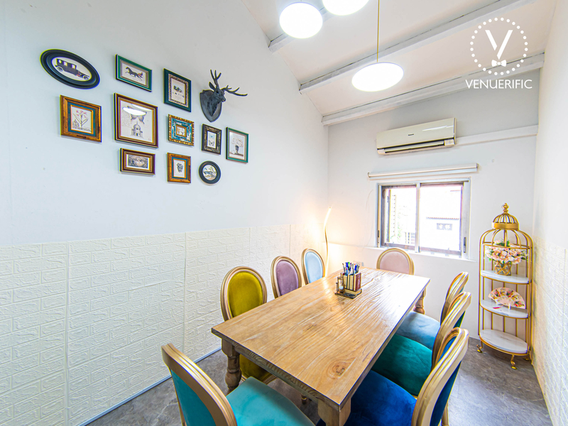 White room with 8 colourful chairs and unique floral and wall displays