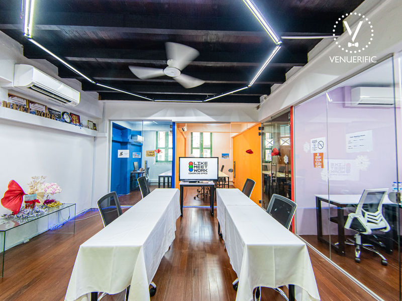 Colourful indoor meeting venue with long tables and chairs