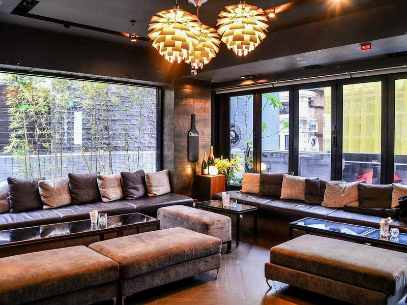 indoor seating area with cushions and hanging lights