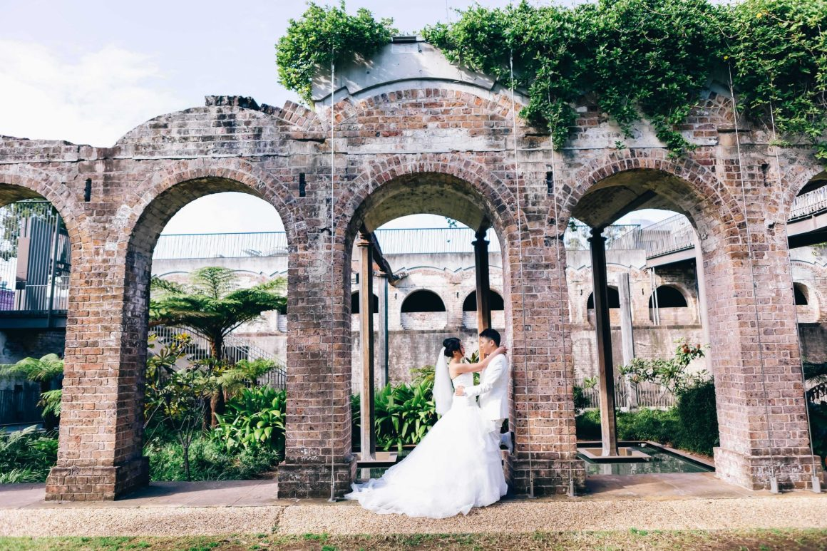 wedding couple posing with brick walls for a photo shoot
