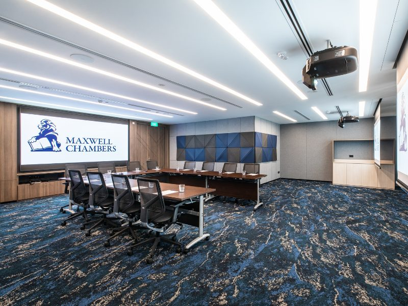 Indoor meeting room with screen and boardroom table and chairs