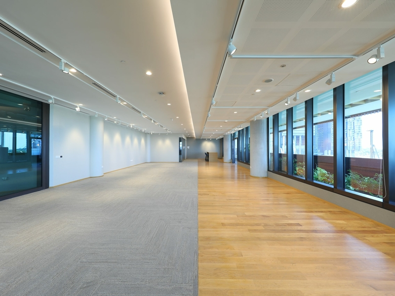 Large spacious room divided into two with one side with windows and wood floor, the other side with carpet and lighting